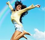 Young Beautiful Woman Jumping To The Sky.