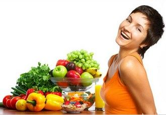 Young healthy woman laughing with fruits and vegetables.